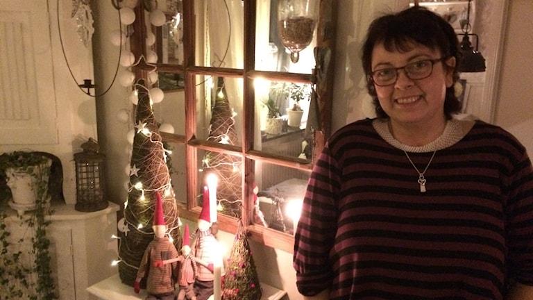 Susanne Nilsson står i sitt julpyntade hus med tända ljus i bakgrunden.