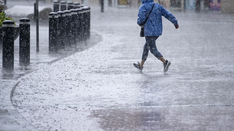 Regn på gata. Person springer för att ta skydd.