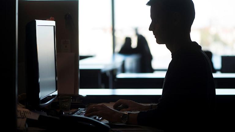 Siluett av en man som sitter vid en dator.
