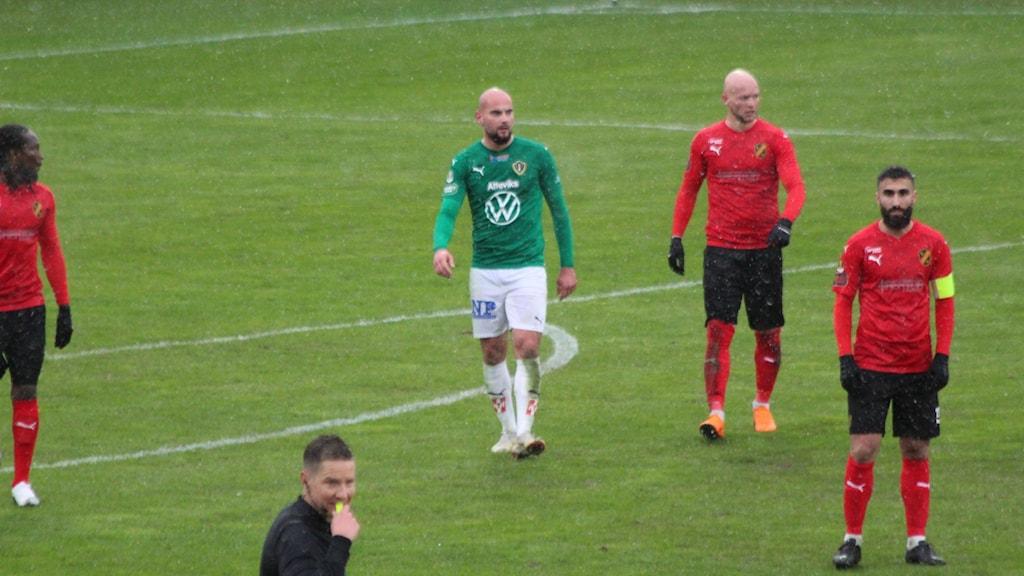 En fotbollsspelare i grön tröja.