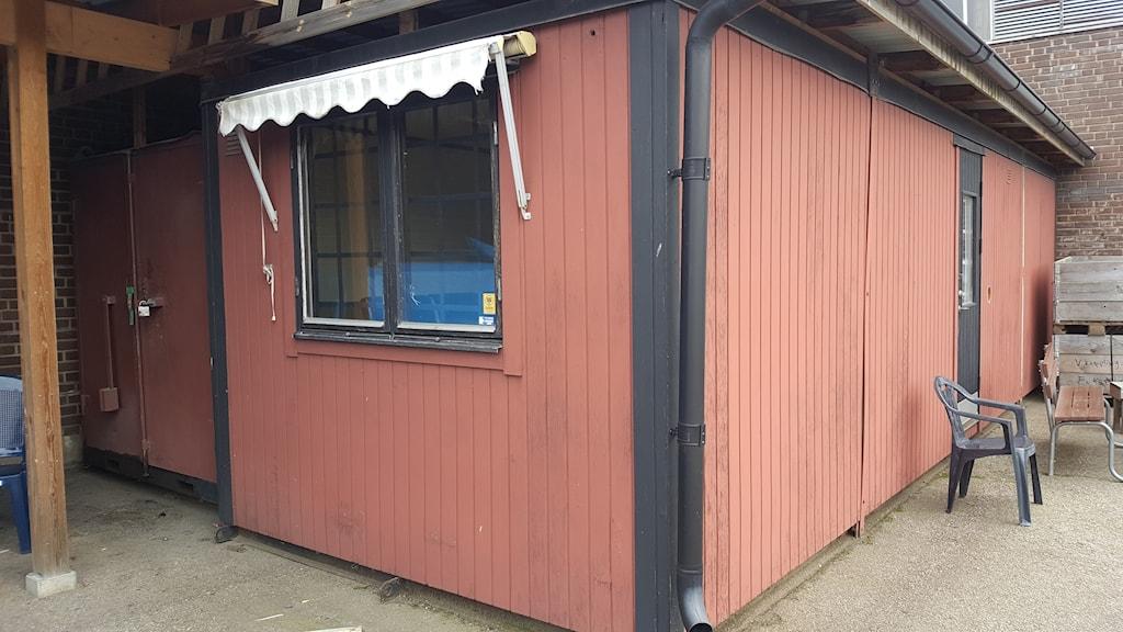 En röd barack med svarta knutar.