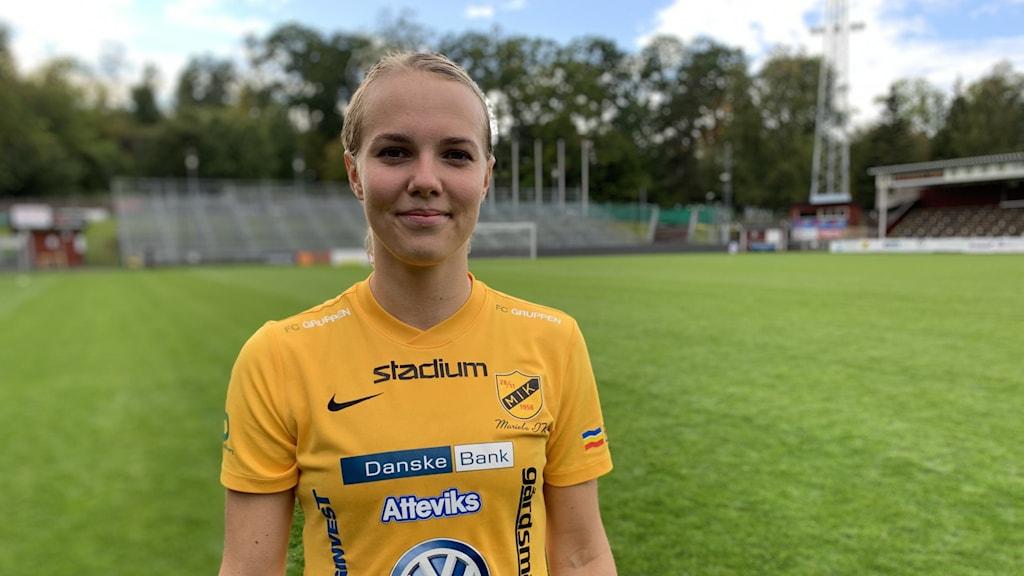 En kvinna med gul fotbollströja.