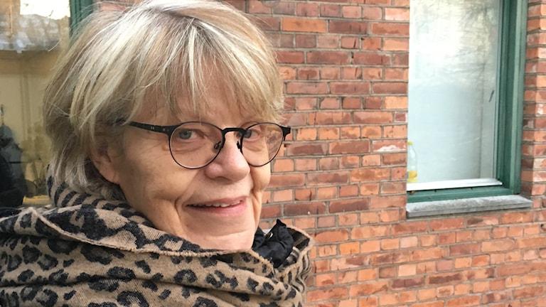 Kvinna står utomhus med halsduk och täckjacka