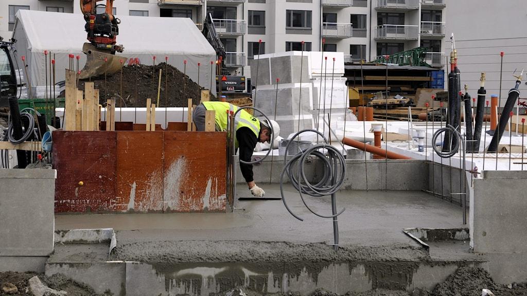 Man som gjuter cement vid bygge.