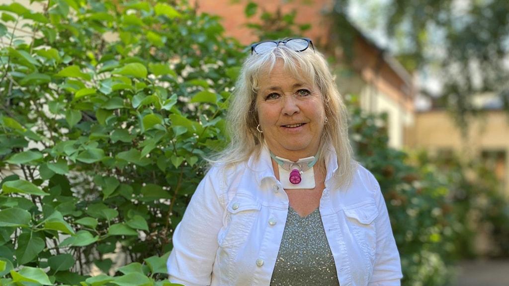 Kvinna står framför grön buske.