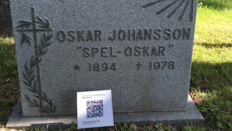 En gravsten med en QR-kod i förgrunden.