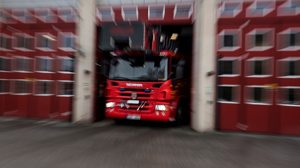 En brandbil kör ut ur ett garage.