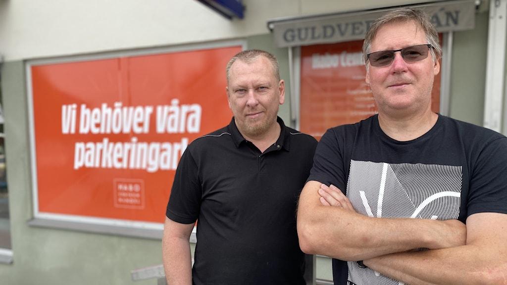 """Christer Alzén och Niklas Karlsson framför en orange skylt med texten """"Vi behöver våra parkeringar""""."""