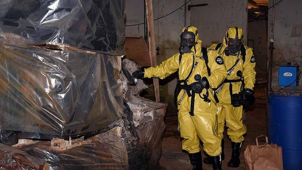 Klädda i gul skyddsdräkt inspekterar förorenad industri.