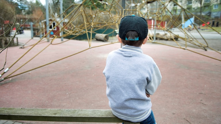 Ensamt barn vid lekpark.