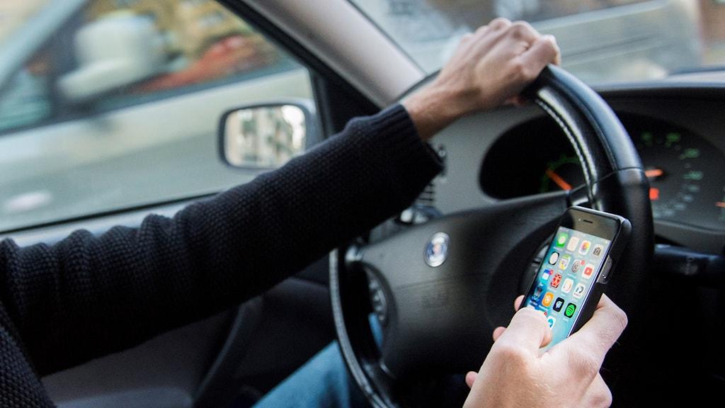 En person kör bil och använder sin mobil samtidigt.