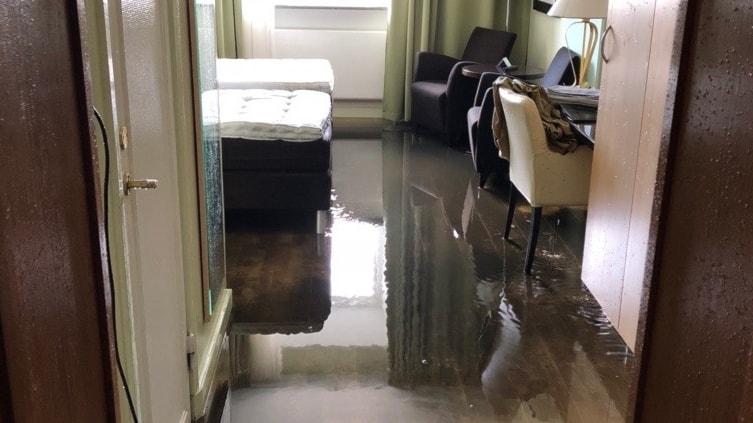 Ett hotellrum med massa vatten på golvet.