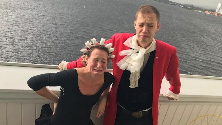 Hanna Schön och Kalle Malmberg står på en balkong och ser ledsna ut