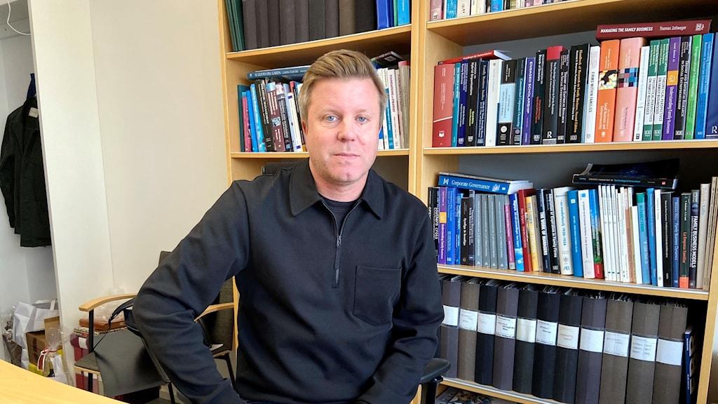 Mattias Nordqvist i sitt kontor, framför en hylla med böcker och pärmar.