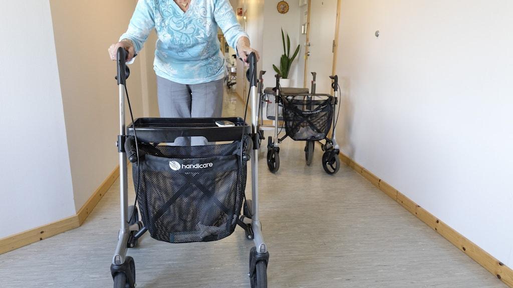 Äldre kvinna med rollator i korridor.