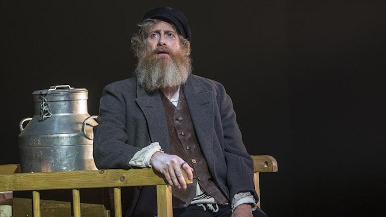 Huvudrollsinnehavaren Per-Johan Persson tittar ut över teaterscenen under uppsättningen av Spelman på taket.
