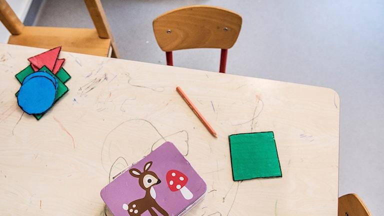 En bänk och en tom stol på en förskola.
