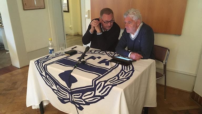 Två män sitter vid ett bord täckt av en IFK Värnamo-flagga.