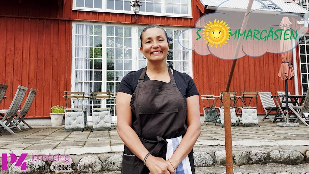 En leende kvinna står framför ett hus med stora fönster, vita lister och röda träplankor.