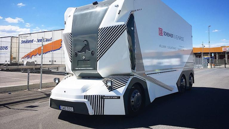 Vit högteknologisk apparat i stor storlek med hjul på väg.