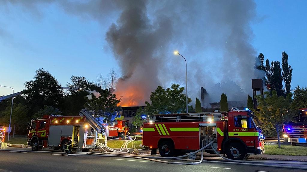 Brand i en kyrka. Två brandbilar står framför.