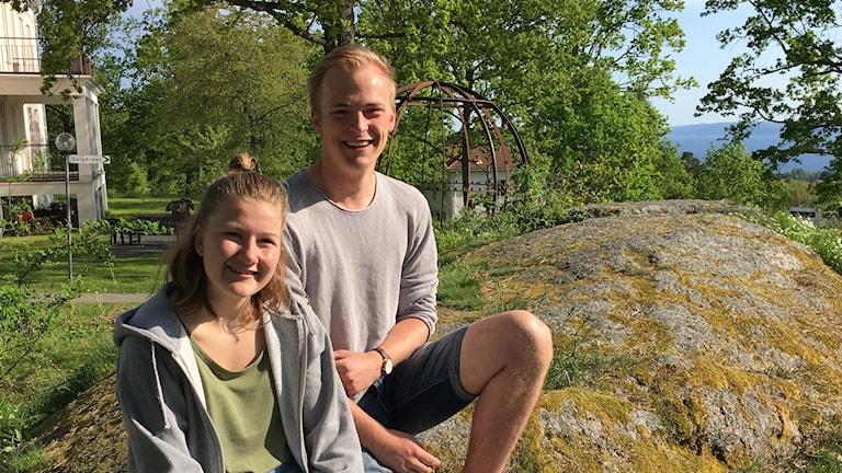 Två ungdomar sitter i solen på en sten.