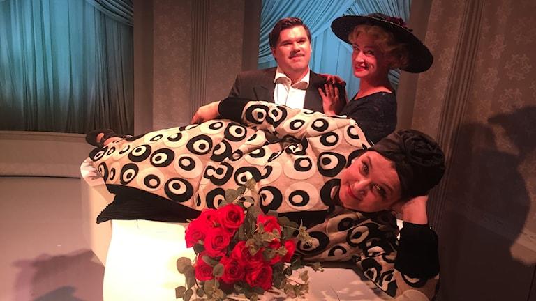 Tre skådespelare från föreställningen. Miss Foster ligger på en vit flygel.