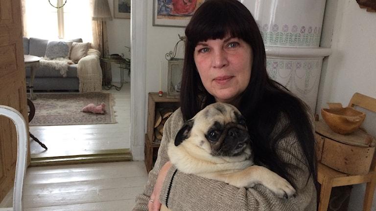 Katarina Bergström sitter i sitt kök i Sävsjö. I famnen har hon sin lilla hund.