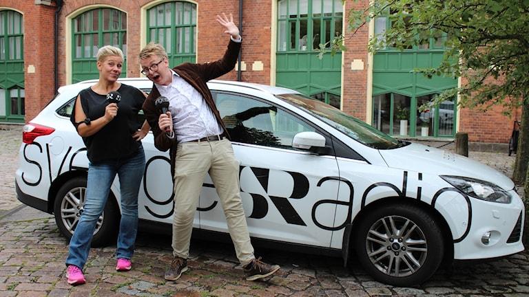 Sanna och Malte står och är glada med mikrofoner i händerna, framför Sveriges Radio-bilen.