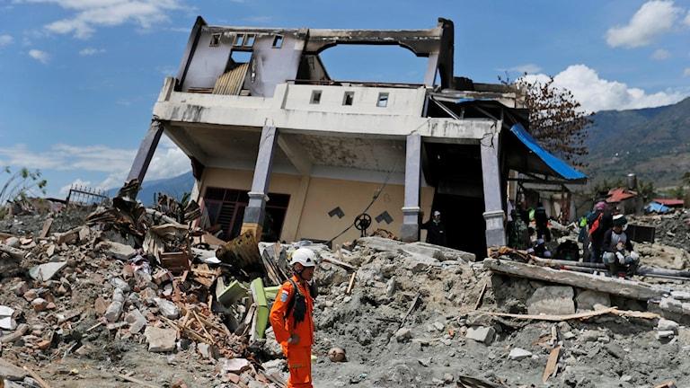 En byggarbetare står framför ett rasat hus.