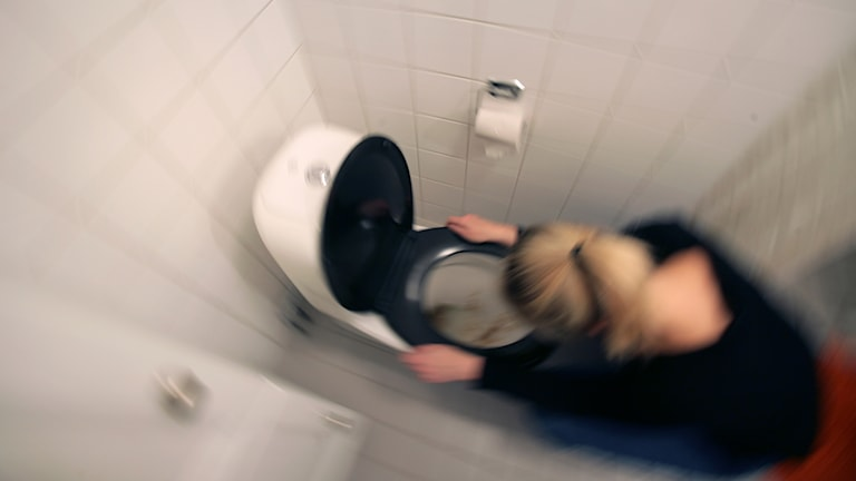 En person hukar sig över en toalett.