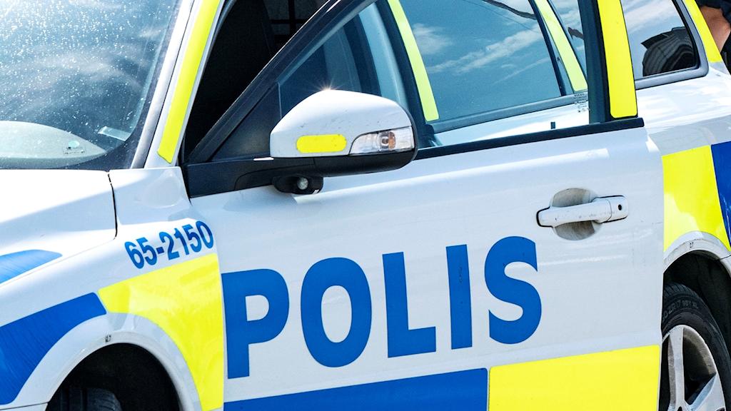 En polis står bakom en polisbil