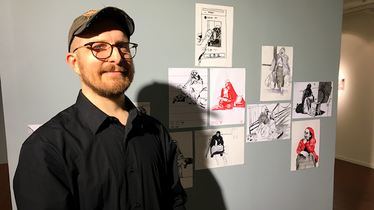 Åke Sjöberg står framför några av sina konstverk.