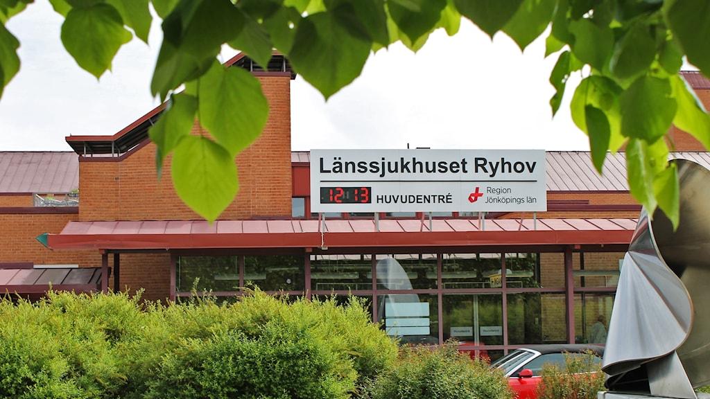 """En skylt med texten """"Länssjukhuset Ryhov"""" inramad av grönska."""