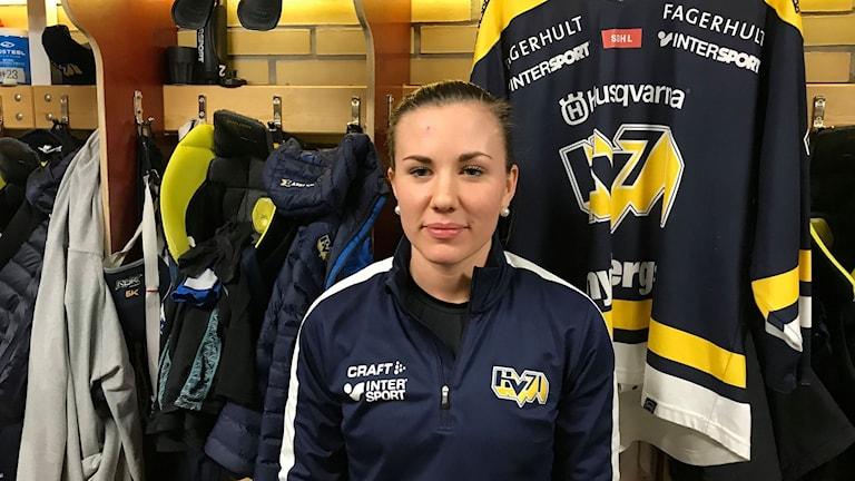 Anna Kjellbin i kläder med HV71-logo på i omklädningsrum.