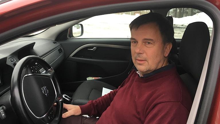 Rolf Bogmark sitter på förarplatsen i en bil.
