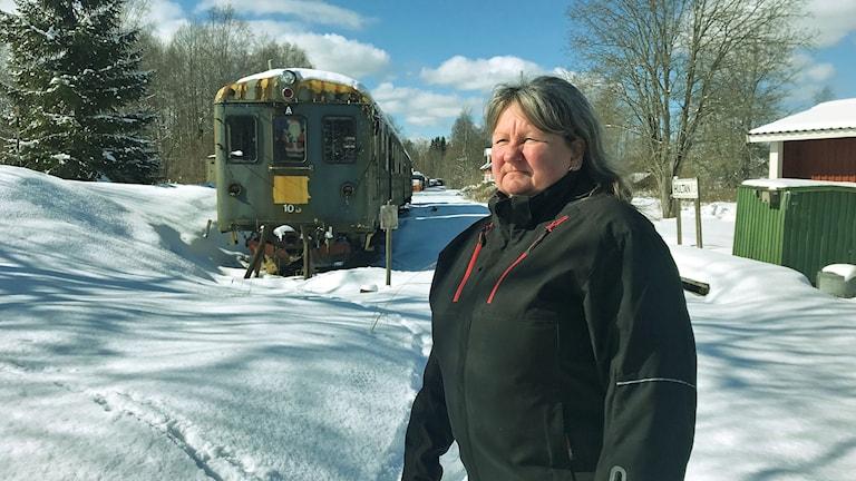 Carita Hammarström framför gamla tågvagnar i Hultanäs.