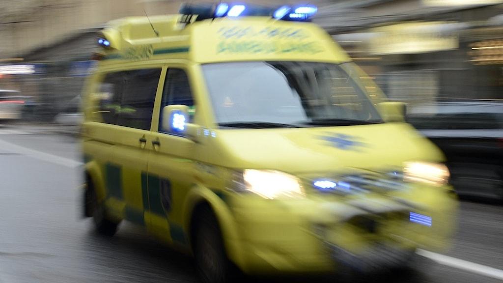 Gul ambulans kör snabbt på väg.