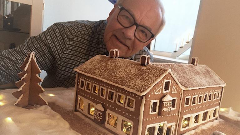 Bengt Bonving bakom sitt pepparkakshus som ser ut som textilhuset i Nässjö.