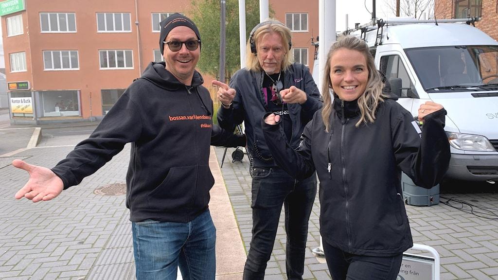 Tre personer står och ler och visar sig starka in i kameran