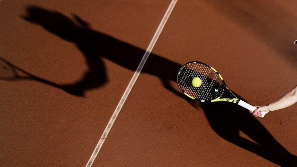 Ett tennisracket på grusplan