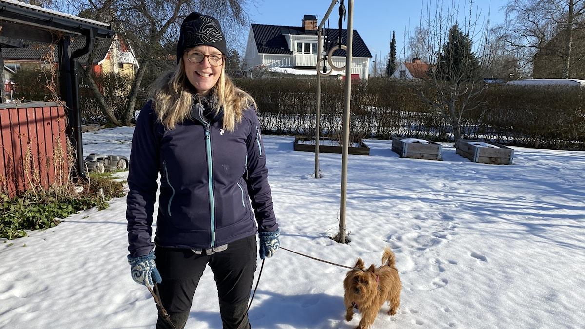 Kvinna står med hund utomhus i snö