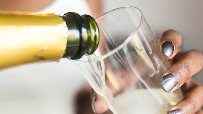 En kvinna häller upp ett glas champagne.