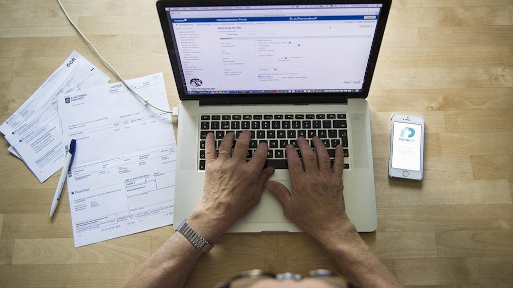 En äldre man sitter vid en laptop med papper och mobil framför sig.