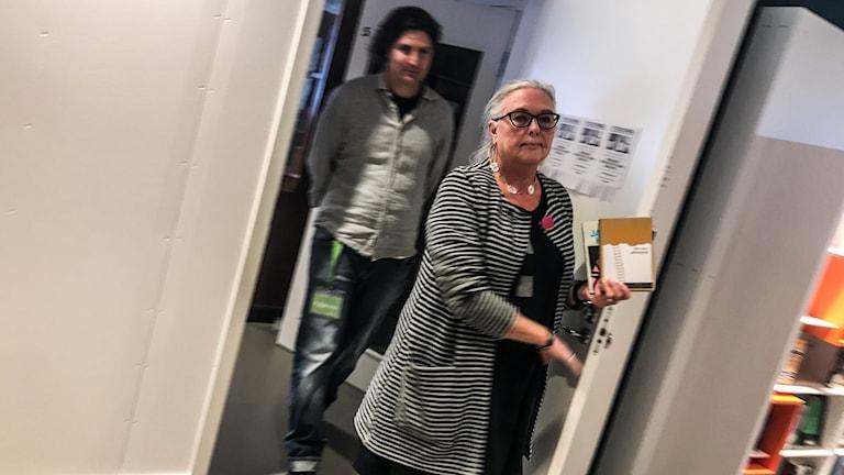 Bibliotekarierna Ewa och Mårten kommer ut genom en dörr.