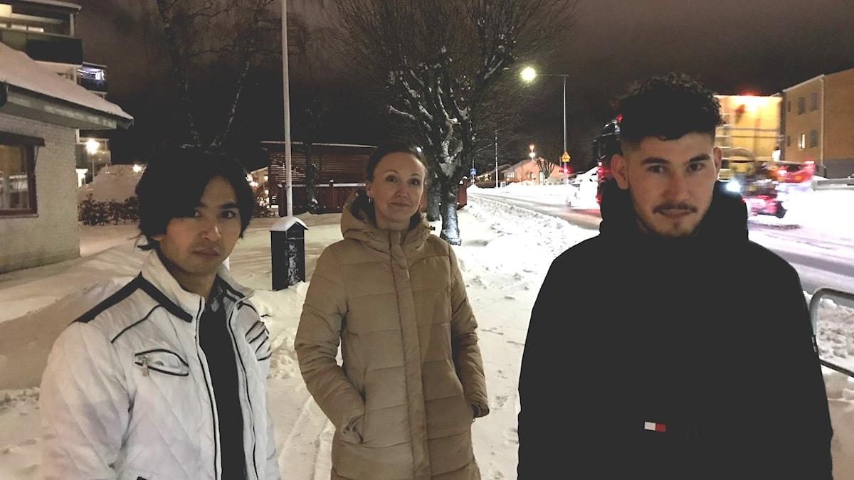 Två killar står i vinterjackor utomhus och tittar in i kameran. Bakom dem står en tjej i beige vinterjacka.