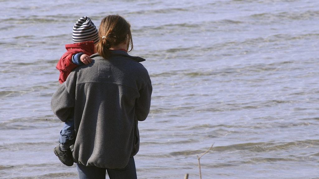Mamma med barn i famnen vid havet