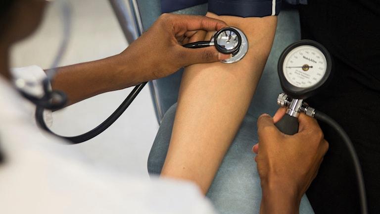 Närbild på en blodtrycksmätare som hålls mot en arm.