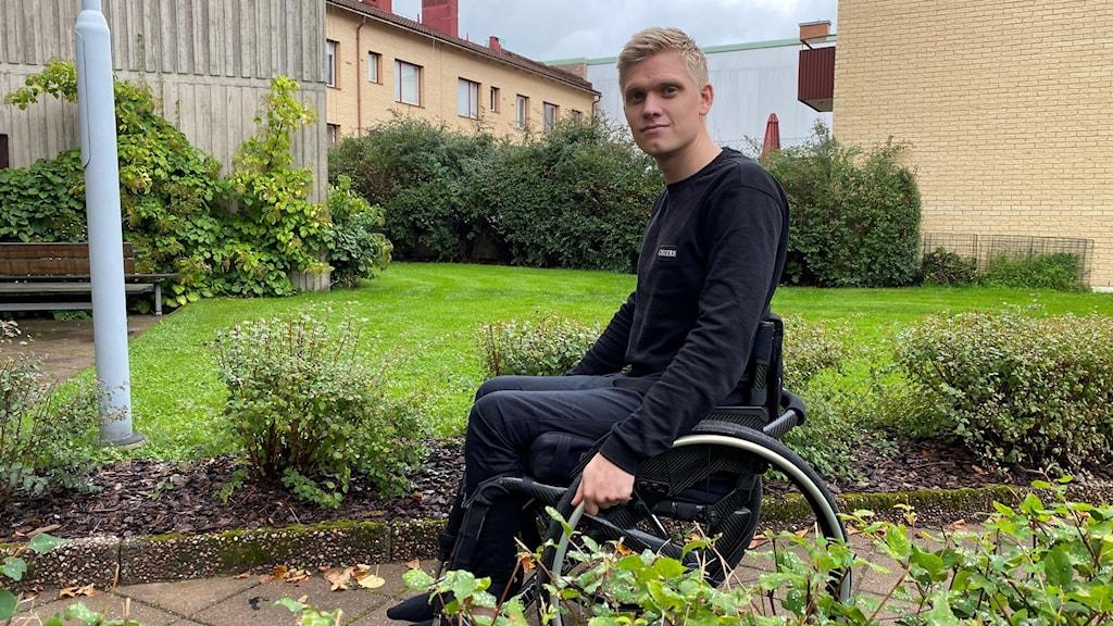 Ung man i rullstol i en trädgård utanför ett flerfamiljshus.