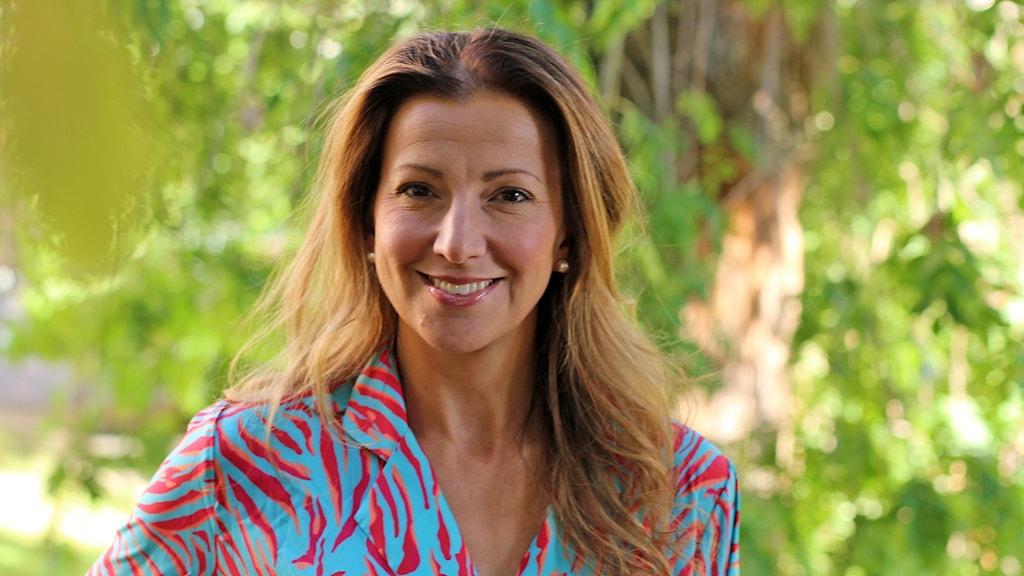 Sonja Aldén fotograferad utomhus i höstljus. Står framför mur av gröna blad